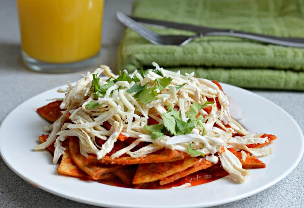 Chilaquiles made with a base of freshly cooked, homemade tortilla chips that are then submerged in a flavorful tomato and dried chile salsa, resulting in a delicious, smoky flavor.