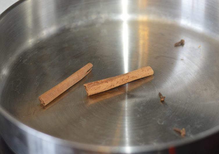 Arroz con leche adding the cinnamon and cloves