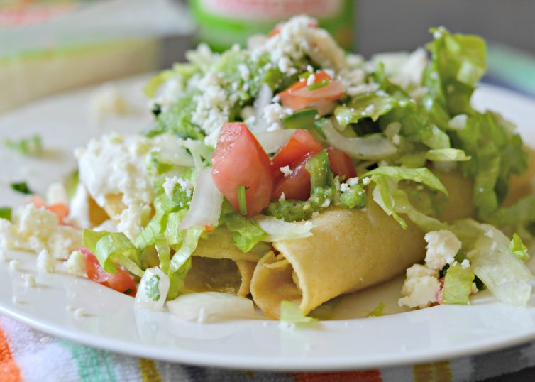 Crispy Potato Flautas are filled with creamy mashed potatoes, fried until golden brown, and topped with lettuce, pico de gallo, salsa, queso fresco and crema.