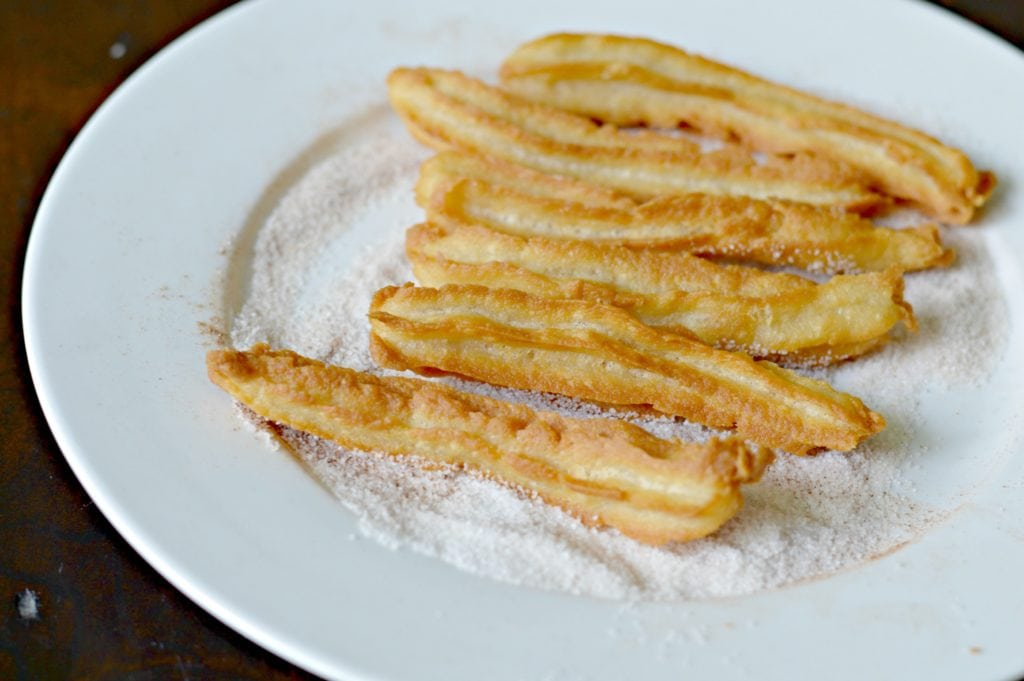 Coating Churros in Cinnamon Sugar