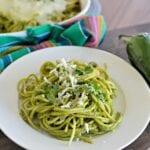 Espagueti verde en un plato con queso y cilantro