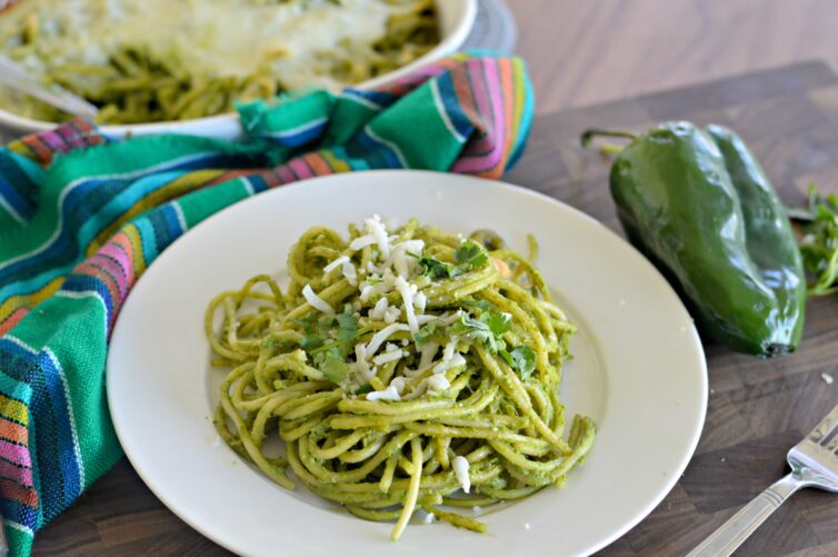 Green spaghetti made with poblano peppers on a white plate with colorful tablecoth (espagueti verde)