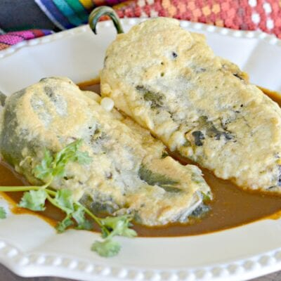 Picture showing chiles rellenos de queso in a bed of ancho chile salsa garnished with cilantro