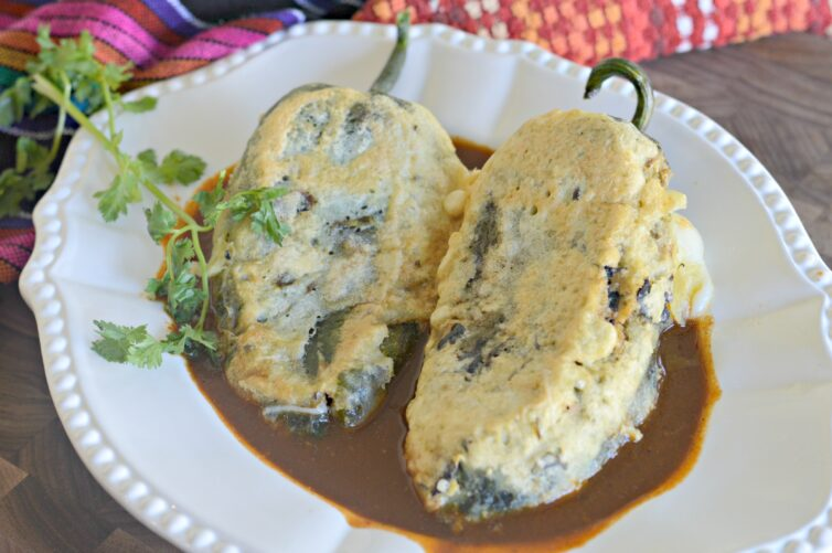 Chiles rellenos de queso on a white plate with an ancho chile salsa garnished with cilantro