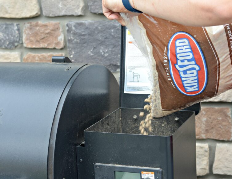 My husband adding Kingsford 100% hardwood pellets into the wood pellet grill's hopper