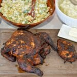 Smoked whole chicken on a cutting board with salad, corn and mashed potatoes in the background
