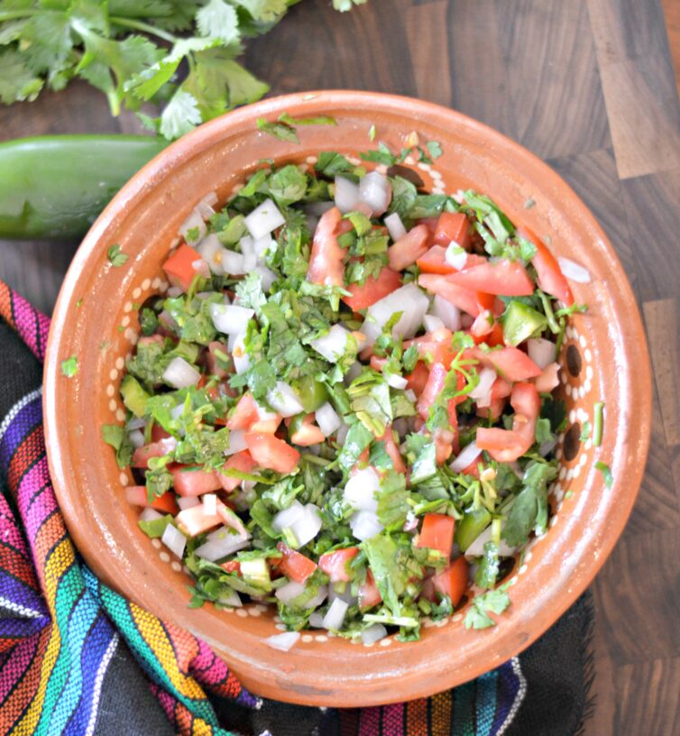 Pico de gallo in a bowl with a jalapeno next to it