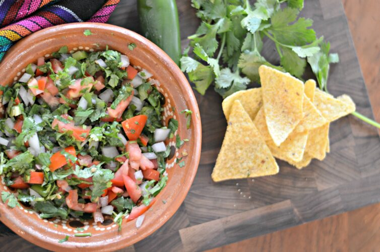 Pico de gallo in a brown bowl on a table with chips next to them