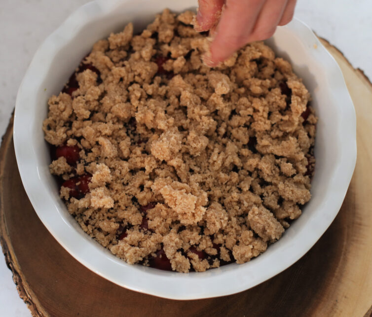 Adding the crumble to the cherry cobbler before baking it