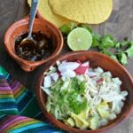 Pozole blanco in a brown bowl with hot salsa and tostadas