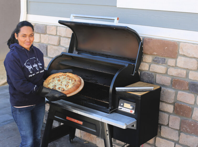 me holding a smoked pizza by a traeger timeberline 1300
