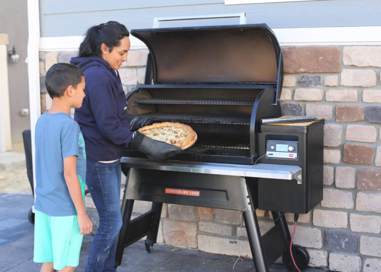me and my son taking pizza off of the traeger